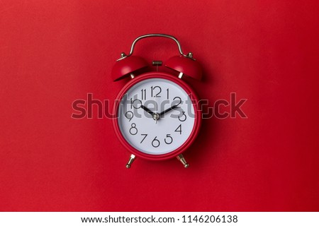 Photo of  red alarm clock on red background. close up shot. top view.