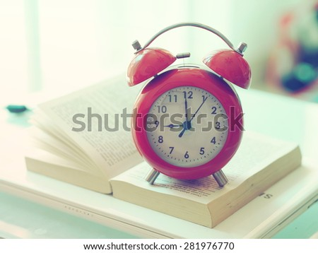 red alarm clock on the book vintage color