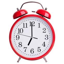 Red alarm clock shows exactly seven o'clock