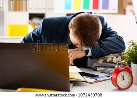 Red alarm clock shows late time closeup and tired office male clerk in suit take nap on table workplace full of exam papers. Career frustration freelance employment fail study problem low energy down #1072430708
