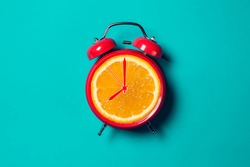Red alarm clock with orange fruit on the place of watch dial.