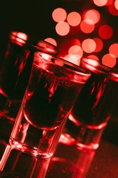 Red alcohol cocktails in shot glasses over red bokeh light  background. Shots on bar counter in night club party.