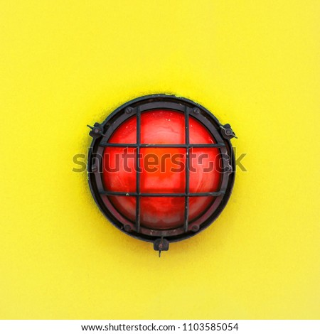 Red alert bulkhead light fixed to a painted yellow orange colour wall background. Photo in square format.