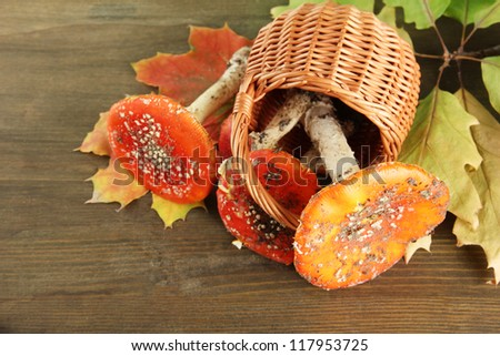 red amanitas in basket, on wooden background