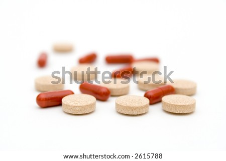 Red and beige medicine pills spread on white background