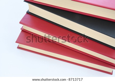 Red and black books stacked on top of each-other isolated on white background