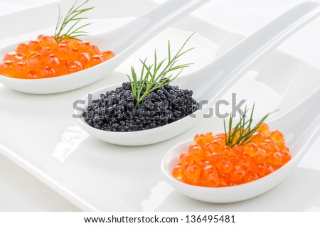 Red and black caviar on porcelain spoons