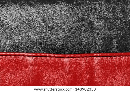 Red and black colored stitched leather close up with seam