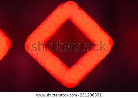 Red and black defocused light background, illumination bokeh of rhombus