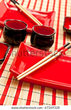 Red and black empty sushi set on the bamboo background
