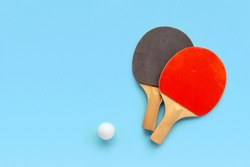 Red and black rackets for table tennis with white ball on blue background. Ping pong sports equipment in minimal style. Flat lay, top view, copy space