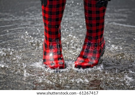 Red and black rubber boots splashing in a puddle after rainfall.