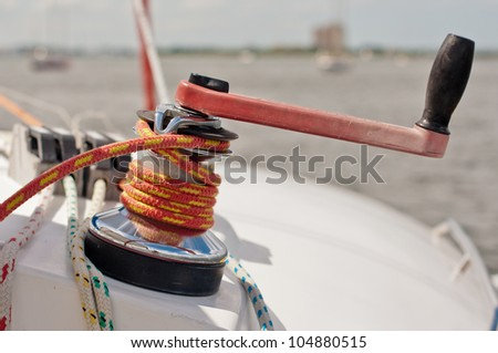Red and black winch handle inserted into large winch with red and yellow line wrapped