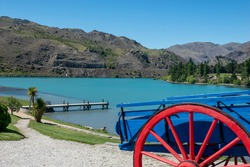Red and blue cart at top of path leading to jetty into turquoise river surrounded by Central Otago hills at Cromwell historic precinct in Central Otago, New Zealand.