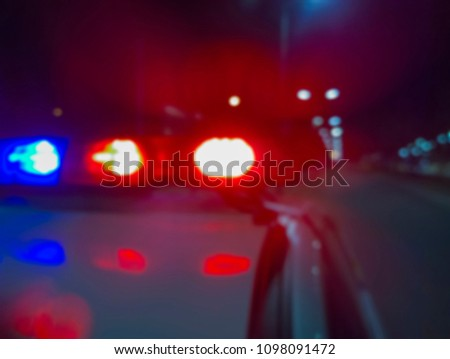 Red and blue flashing police car lights at night, crime scene. Abstract blurry image to illustrate criminal news and events. #1098091472