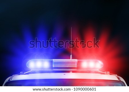 Red and blue light flasher of a police car. Siren on police car flashing. Red and Blue flasher on the police car at night. Dark background.