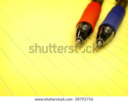 Red and Blue Pens on Yellow Pad of Paper