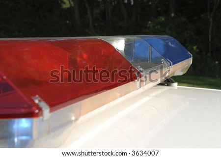 Red and blue police lightbar on white police car.