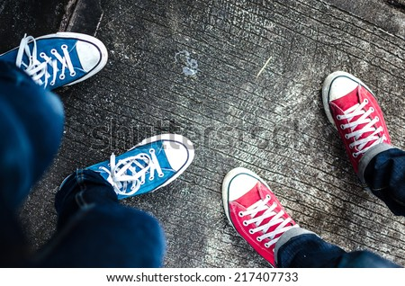 Red and Blue Sneakers shoes walking on Dirty concrete top view , Canvas shoes walking on concrete , two sneakers behind each others as a sign of love , Sneakers shoes Couple