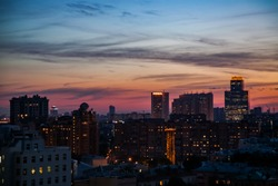 Red and blue sunset with clouds and buildings silhouette in the city.  Moscow