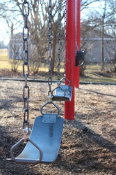 Red and Blue Swing Set on Playground with Fall Trees and Shed in Background