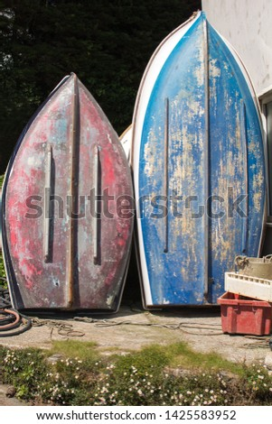 Red and Blue Upturned Dinghies in a Boatyard