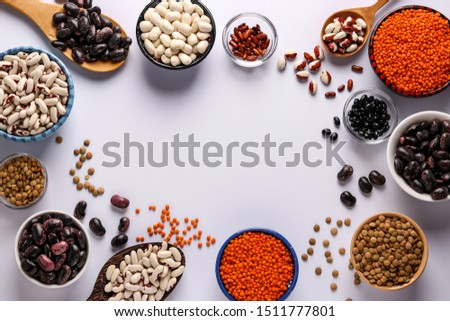 Red and brown lentils, black, brown and white beans are legumes that contain a lot of protein are located in bowls on white background, horizontal orientation, copy space