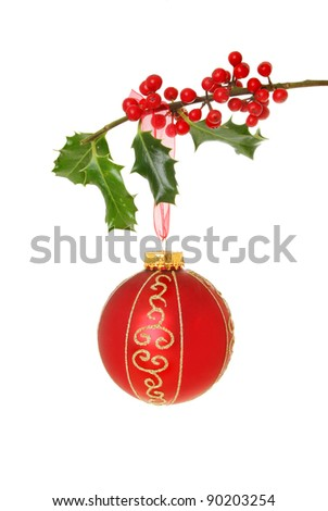 Red and gold Christmas bauble hanging from a holly branch