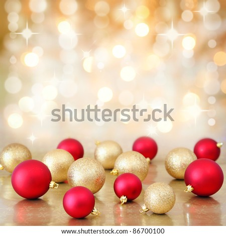 Red and gold Christmas baubles ornaments on background of defocused golden lights. Shallow DOF.