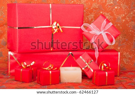 Red and gold gift boxes with a candle on a Xmas background