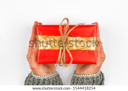 Red and gold gift wrap in the hands. Knitted with a bow on a white background. DIY gift wrap. Woman hands give a wrapped present. Christmas present. View from above.