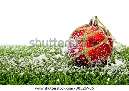 red and golden christmas ball on the grass with snow