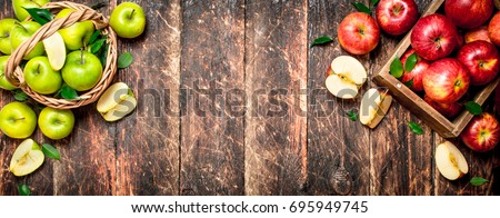 Red and green apples . On wooden background.