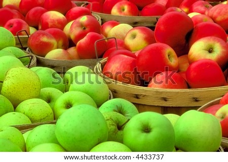 red and green apples sit in bushel baskets in fruit market - stock photo