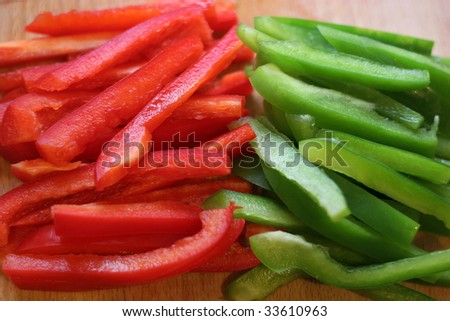 Red and Green Bell Peppers Sliced on a Wooden Chopping Board