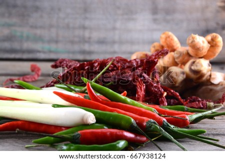 Red and green chilies, dried chilies, lemon grass, turmeric and ginger on rustic wooden base #667938124