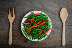 Red and green chilli on  wooden table