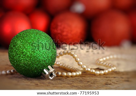 Red and green Christmas balls on an old vintage table with pearls