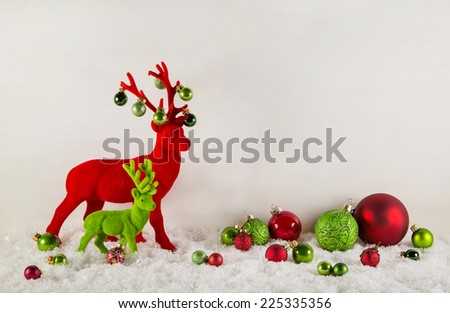 Red and green christmas decoration with snow: Reindeer with balls on wooden white background.