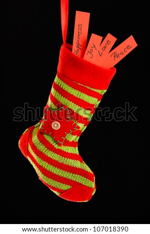 red and green christmas stocking filled with love, joy, peace and happiness
