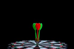 Red and green dart arrow hitting target center Dart board Isolated on black background, Setting aim goal achievement concept challenging business goals And ready to achieve goal and Marketing concept