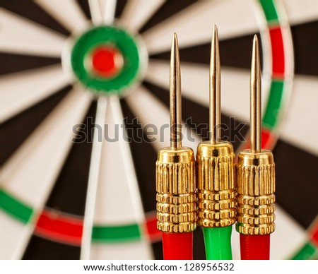 Red and Green Darts and a Dart Board in narrow focus (Original image of the world is a public domain image from NASA)