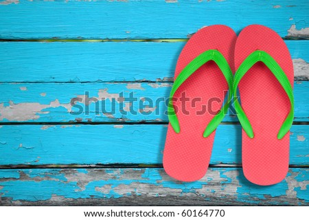 red and green flip flop sandals on blue wood