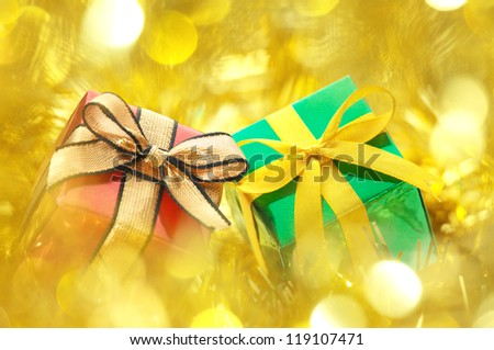 Red and green gifts on gold blurry lights background.