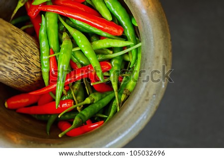 Red and green pepper in mortar.
