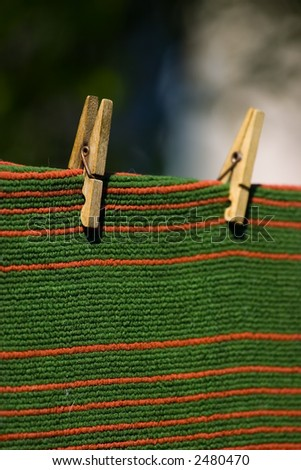 Red and green striped carpet pegged to a clothesline. Place for copy text