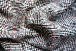 Red and grey Glen check woolen fabric in soft folds