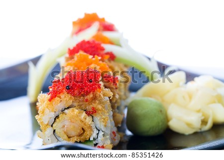 Red and orange fish eggs or tobiko on crunchy seafood sushi rolls at an Asian food restaurant.