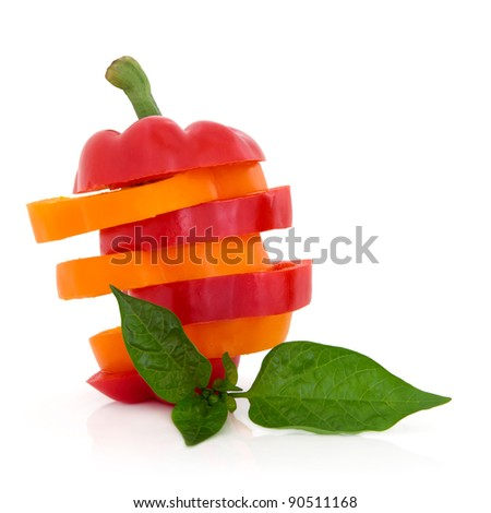 Red and orange pepper vegetables sliced in a stack with leaf spring isolated over white background.