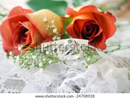 stock photo Red and orange rose on lace with wedding bands